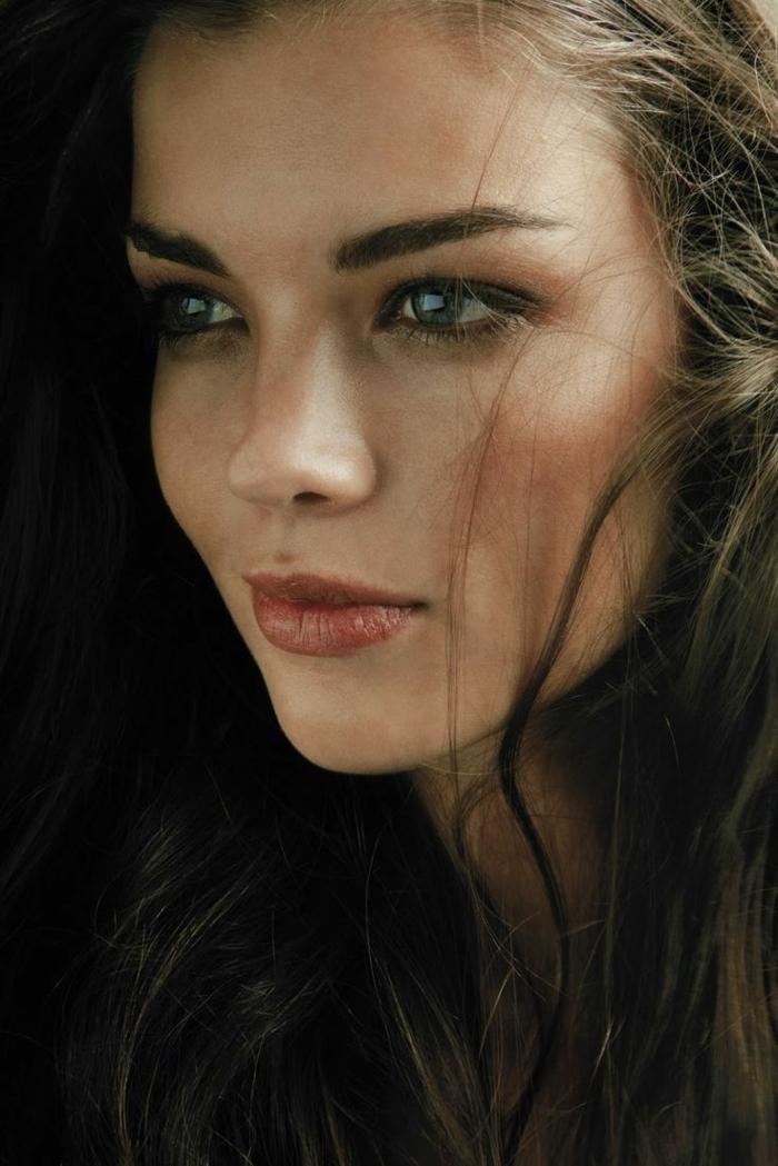 rouge à lèvres orange et yeux légèrement soulignés, cheveux épais couleur chatain