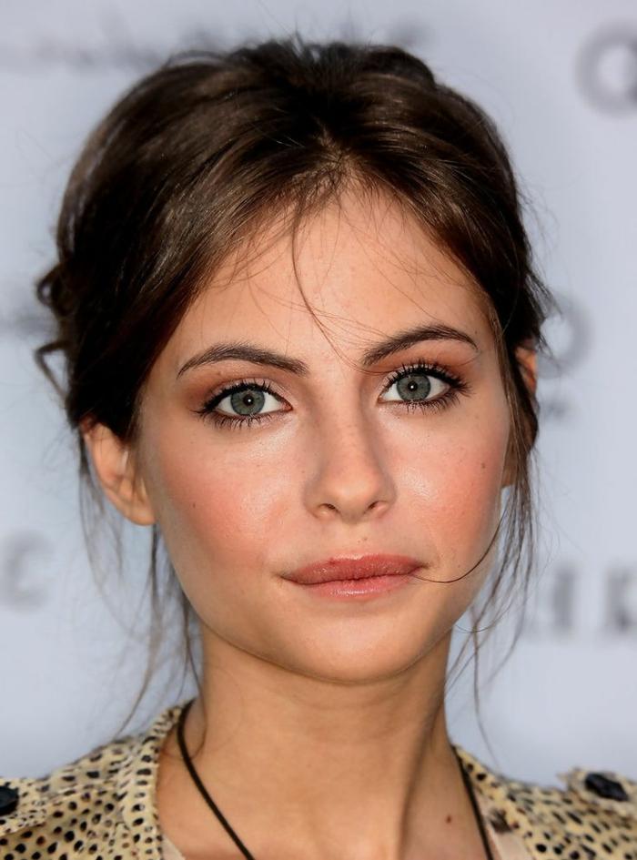 maquillage yeux rose, lèvres oranges, cheveux chataîn foncé, trait d'eyeliner fin