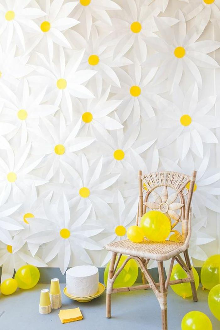 une idée pour habiller un mur pour une fête, des grandes marguerites en carton blanc et jaune, chaise en osier tressé sans accoudoirs, dossier orné avec un grand motif fleur, plusieurs ballons jaunes, sol recouvert de dalles grises