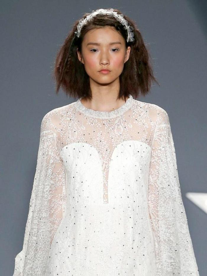 mariée sur les podiums, headband cheveux courts avec des petites fleurs blanches en tissu, carré long, épaules et manches transparentes avec des petits pois en pierres Swarovski
