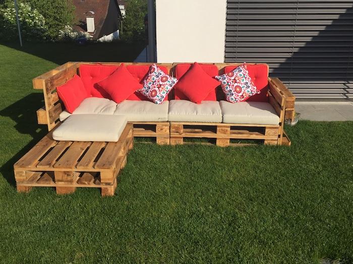 meuble avec palette en bois, un canapé bois brut avec des coussins d assise beige et coussins décoratifs rouges, gazoon vert