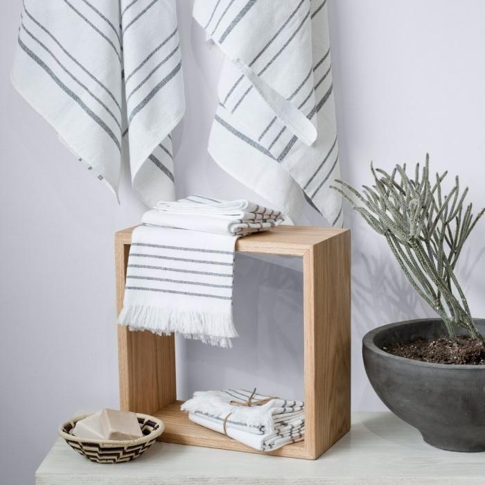 arrangement de salle de bain de style relaxante avec un set de serviette de bain en blanc et noir sur un meuble de bois clair