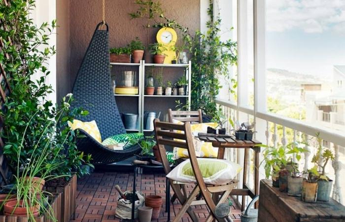 oasis sur le balcon avec mobilier de jardin en bois foncé et une chaise suspendue noire couverte de coussins à motifs tropicaux