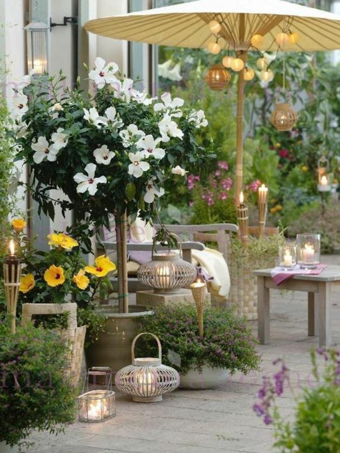 amenagement exterieur en style asiatique, parasol couleur blanc crème, trois lanternes posées au sol, deux bougeoirs sur la table, arbrisseaux fleuris en jaune et blanc