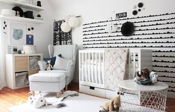 design intérieur stylé dans une chambre bébé aux murs blancs avec déco noire et étagères de bois peintes en blanc