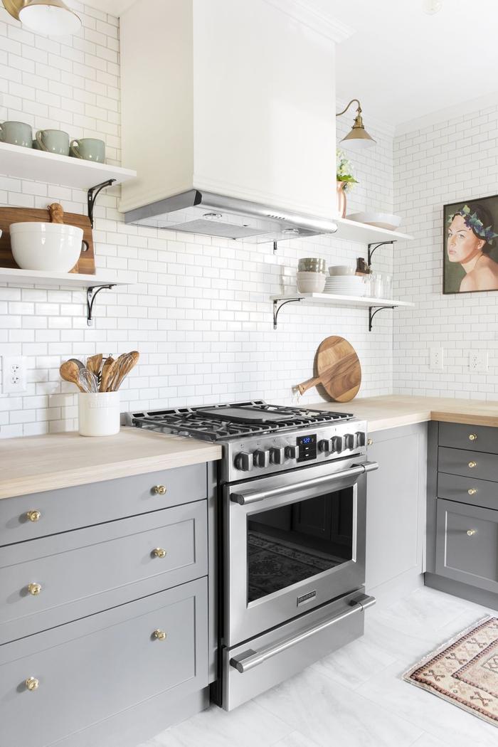 une cuisine grise et bois de style scandinave qui utilise le carrelage mural blanc et le sol effet marbre pour sublimer l espace