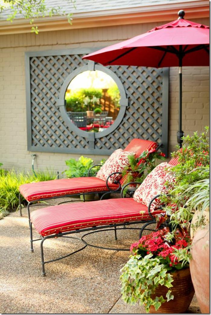 decorer son jardin avec deux chaises-longues aux coussins rouges, un miroir rond en style baroque positionné sur une pergola, parasol rouge, jardin deco, amenagement jardin