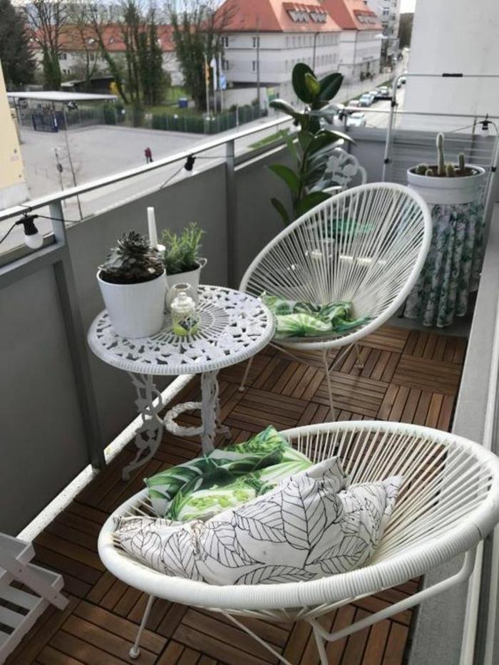 idée déco appartement, deux chaises ovales design en métal blanc avec des dossiers en fils tressés, une petite table ronde avec plan en métal blanc aux décorations incisions en arabesques, sol recouvert de parquet en bois en forme de carrés