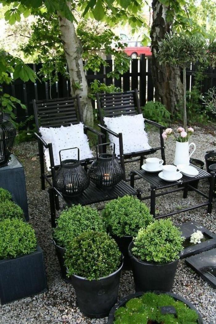 amenagement jardin paysager, coin avec des meubles en métal noir, pots noirs en céramique, petits cailloux gris qui recouvrent le sol