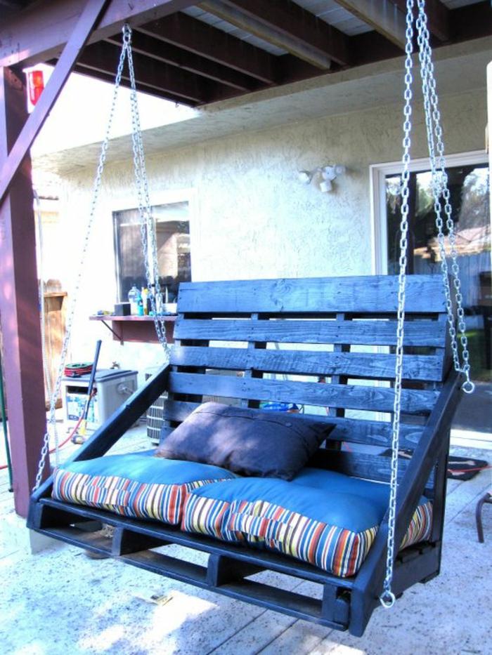 balançoire canapé en palettes peint en noir, avec des chaines en métal couleur argent des deux cotes, meubles de jardin en palettes