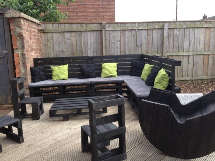 salon de jardin palette avec des pièces peintes en noir, canapé palette, coussins noirs et vert réséda, banquette en palette, chaises avec des dossiers hauts