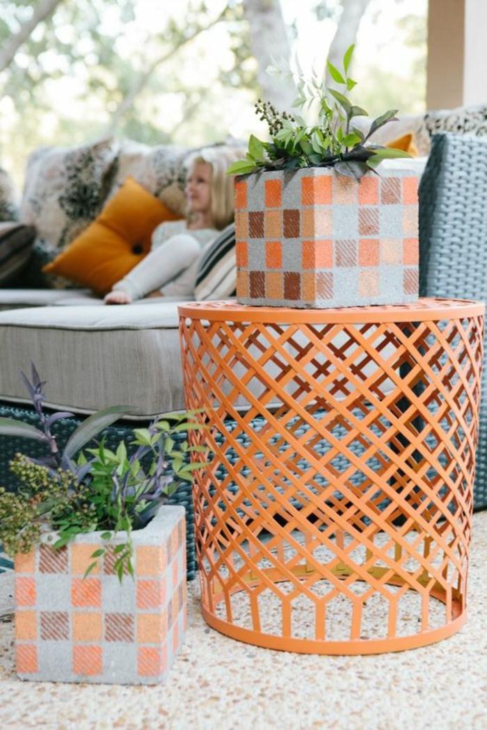 tabouret porte-plante rond en métal orange, deux pots de fleurs en forme carrée ornées de petits carrés en orange et marron, deco jardin pas cher