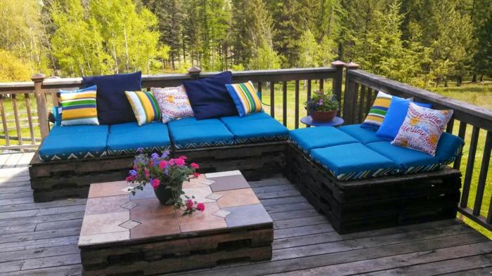 meubles de jardin en palettes, canapé palette, meubles recouverts de coussinets-matelas en bleu roi, des coussins en rayures verticales et horizontales bleu roi et jaune