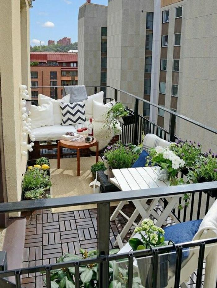 idee deco terrasse, grand balcon avec table pliable blanche, petite table basse ronde en bois marron, sol en dalles graphiques marron, guirlande de lanternes blanches