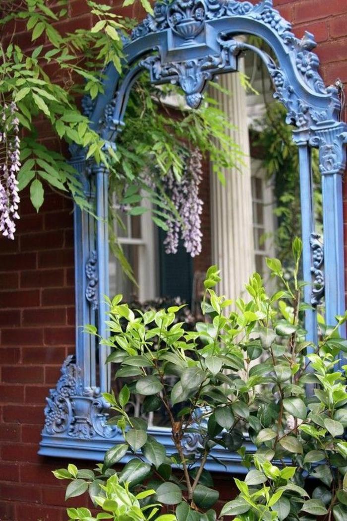 un grand miroir baroque peint en bleu pastel, positionné sur le mur en briques rouges, beau jeu de lumières et d'images, decorer son jardin