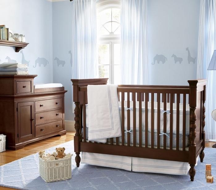 intérieur de style rétro avec peinture murale bleu pastel et mobilier de bois massif foncé dans une pièce au plancher de bois laqué