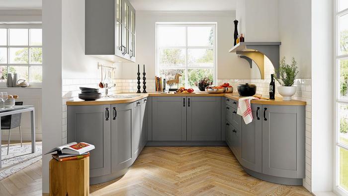 une cuisine grise et bois aménagée en u, aux formes arrondies qui lui confère un air rustique