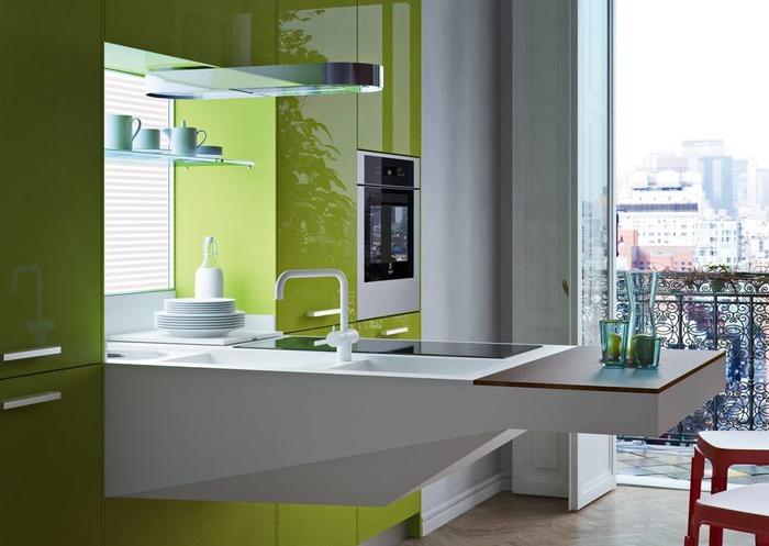 aménagement fonctionnelle et moderne d'une petite cuisine gris clair et vert laqué avec un plan de travail suspendu à évier et planche à découper intégrés
