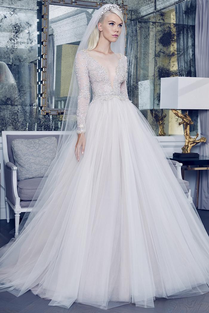 robe de mariée princesse avec une jupe en tulle évasée et bustier avec décolleté asymétrique avec décoration de pierres