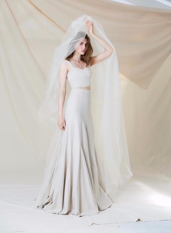 robe de mariée haute couture avec une jupe évasée et un top bustier gris clair avec une voile