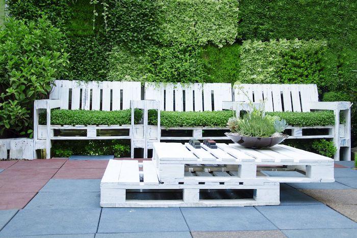 modèle de salon de jardin palette avec un canapé en palette couvert de gazon, table basse en palettes blanches superposées, mur végétal extérieur