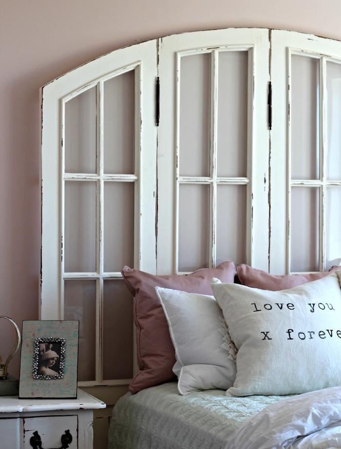 volets de fenetres blancs recyclés en blanc, linge de lit blanc avec coussins décoratifs rose, table de nuit vintage
