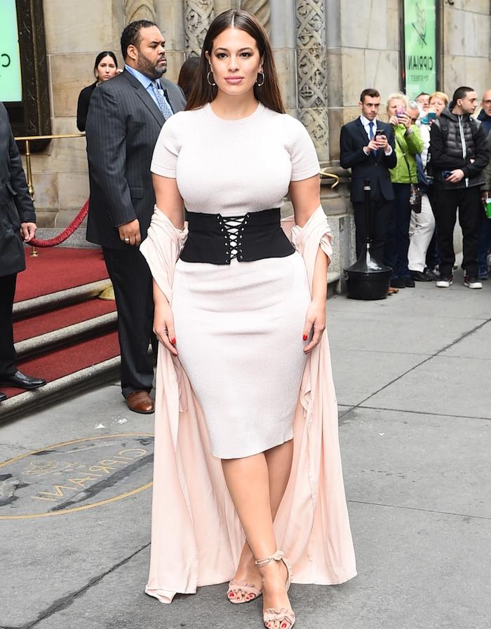 robe grande taille chic femme aux rondeurs, tenue moulante avec ceinture originale, chaussures tendance, veste rose, cheveux chatain lisses