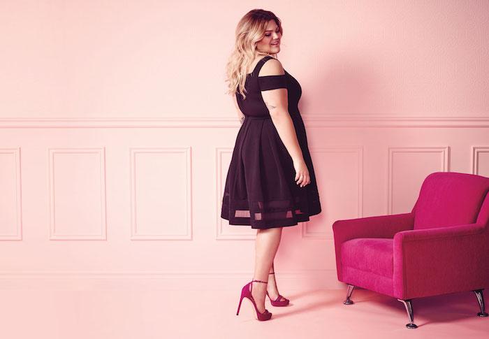 robe grande taille chic couleur noire, chaussures mauves, canapé mauve et fond bleu, fille cheveux blonds