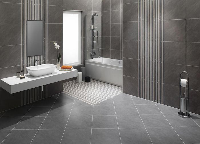 idee de salle de bain carrelée sur sol et murs en gris marbré avec baignoire et meuble lavabo suspendu