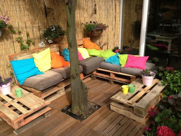 terrasse en bois avec un canapé bois de palette avec coussins d assise gris et coussins décoratifs colorés, petites tables de service en palettes, brise vue en bambou