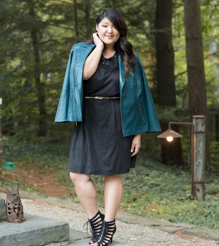 robe grande taille femme chic, couleur noire, veste en cuir bleu pastel, chaussures noires, coiffure cheveux bouclés sur le coté