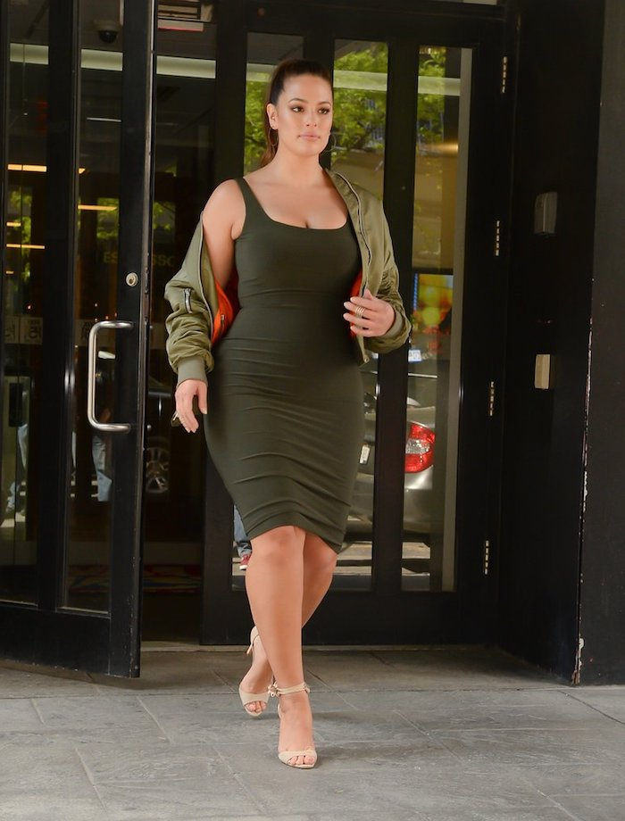 ashley graham avec un exemple de robe pour femme ronde en vert olive foncé et une veste vert olive, queue de cheval haute