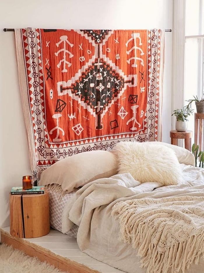 tete de lit tissu orange à motifs azteques, linge de lot blanc et beige, table de nuit rondin de bois, deco chambre cocooning