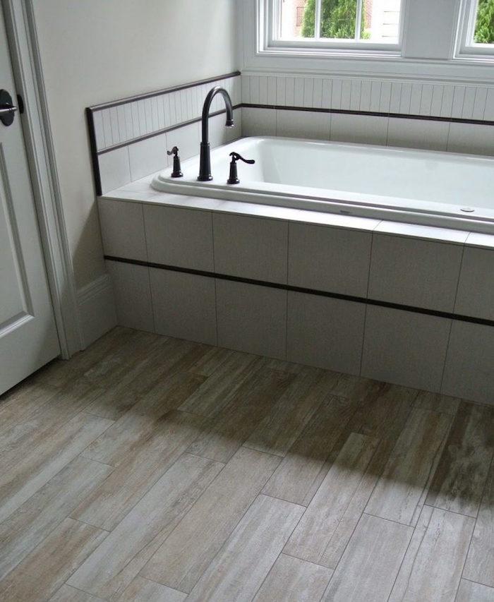 decoration de salle de bain blanche avec parquet faux bois beige clair et baignoire avec faience