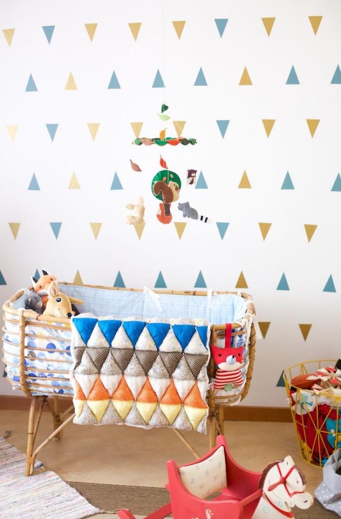 exemple de déco murale dans pièce enfant avec murs blancs, mobile bébé multicolore au-dessus d'un lit-bébé