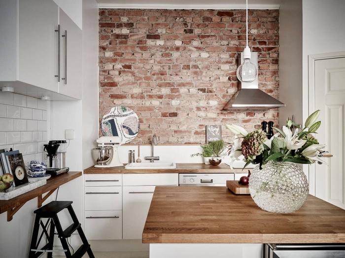 déco de style industriel avec pan de mur en briques rouges dans une cuisine aux armoires blanches avec comptoirs de bois massif