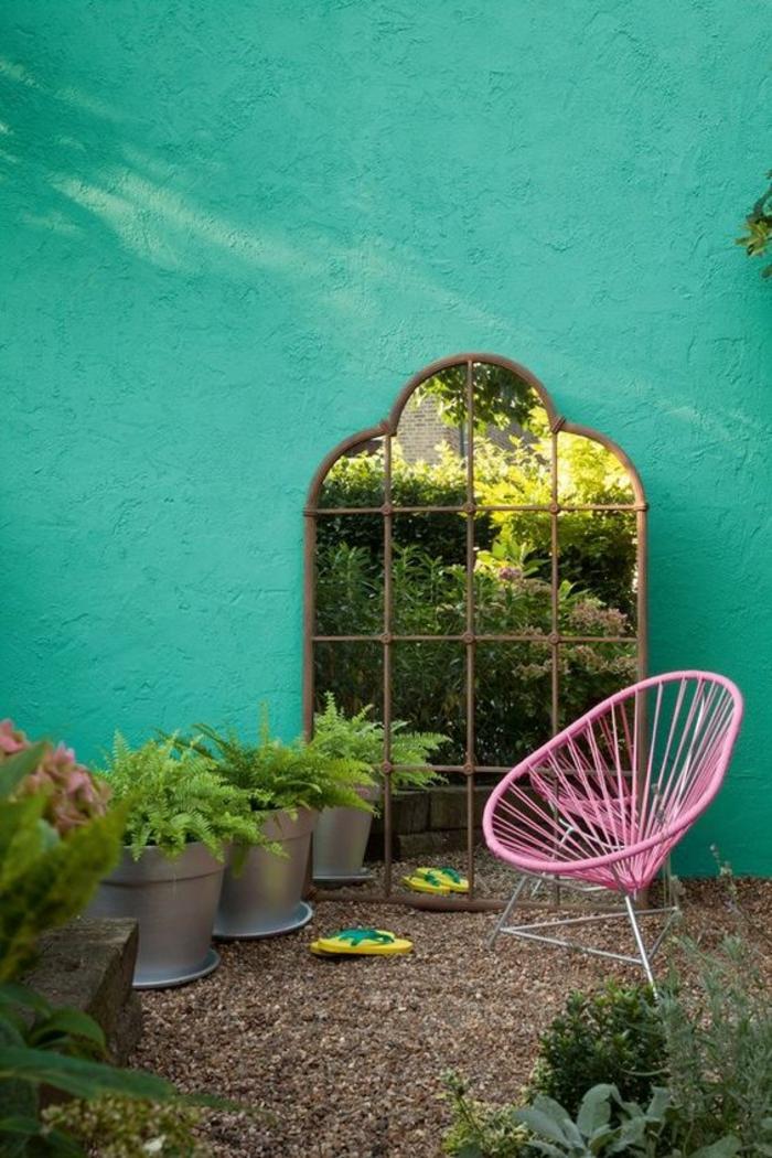 miroir posé par terre dans un coin de jardin, grands sceaux transformés en pots avec des plantes vertes, fauteuil rose en métal, déco jardin récup