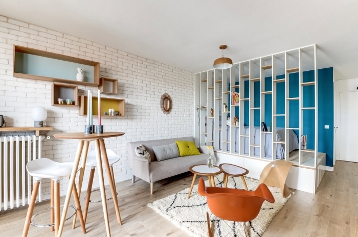 idée déco studio moderne avec revêtement mural en briques blanches et plancher de bois clair, modèle de meuble séparation pièce