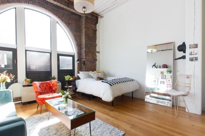 déco de style loft industriel aux murs blancs avec pan de mur en briques rouges et plancher de bois dans un studio étudiant cozy