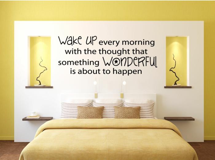 chambre adulte en jaune et blanc, inscription avec message sympa au-dessus du lit, deux niches latérales avec illumination, couverture jaune pour le lit, un pan de mur, decoration murale design
