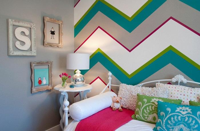 murs aux motifs graphiques en vert canard, blanc et rouge, décoration murale chambre, trois cadres en couleurs différentes sur le mur a cote, lit en métal blanc en style vintage, idee deco mur