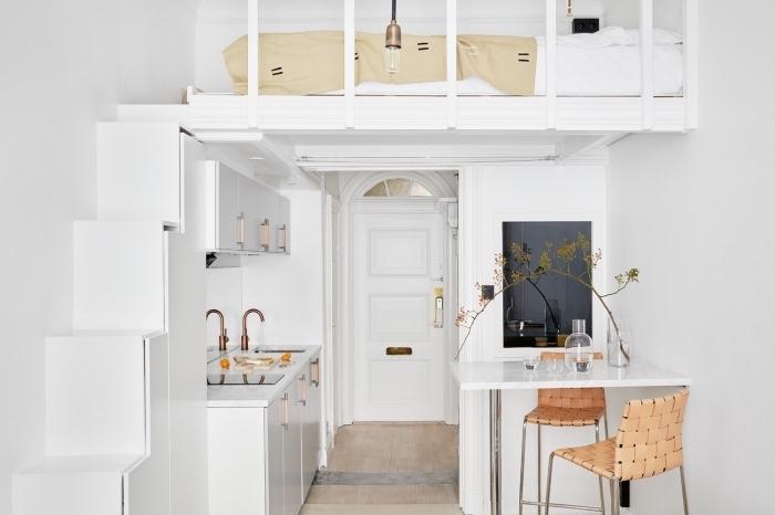 idée aménagement studio avec un lit mezzanine et petite cuisine blanche équipée d'un coin à manger avec ilot et chaises