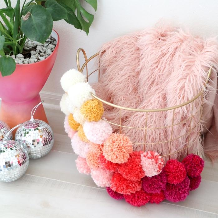 customiser son panier de rangement avec boules de laine de couleurs rouges et pastel, plante verte dans pot à fleur à design ombré