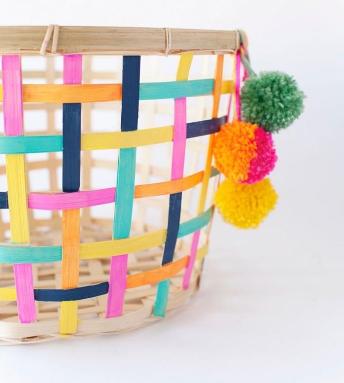 idee deco maison avec un panier peint en couleurs différentes et décoré avec quelques pompons de laine colorés