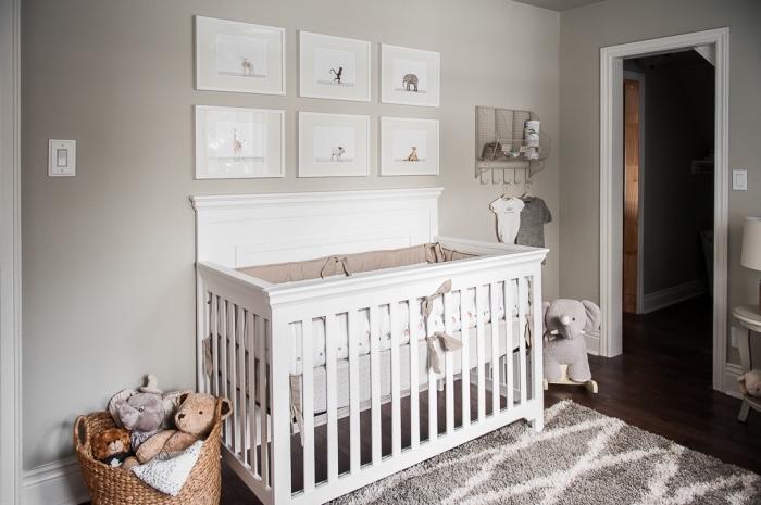 décoration murale chambre bébé beige avec mur de cadres blancs et photos à design animal, rangement jouets dans panier en paille