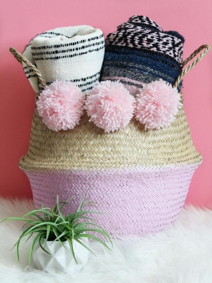 idée comment customiser un panier en paille avec peinture de nuance rose pâle et pompons en laine rose pastel