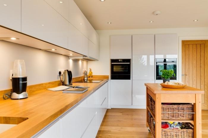idée décoration moderne dans une cuisine blanche laquée avec meubles sans poignées et plan de travail en bois