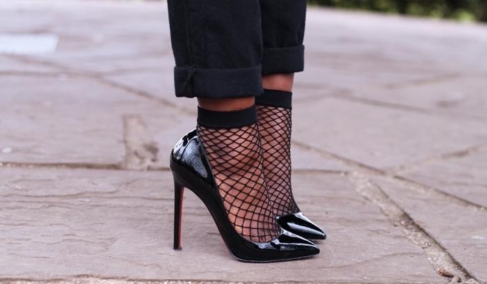élégance et sex-appeal avec une paire de chaussure vernis noir à talons hauts portées avec chaussette filet et pantalon noir