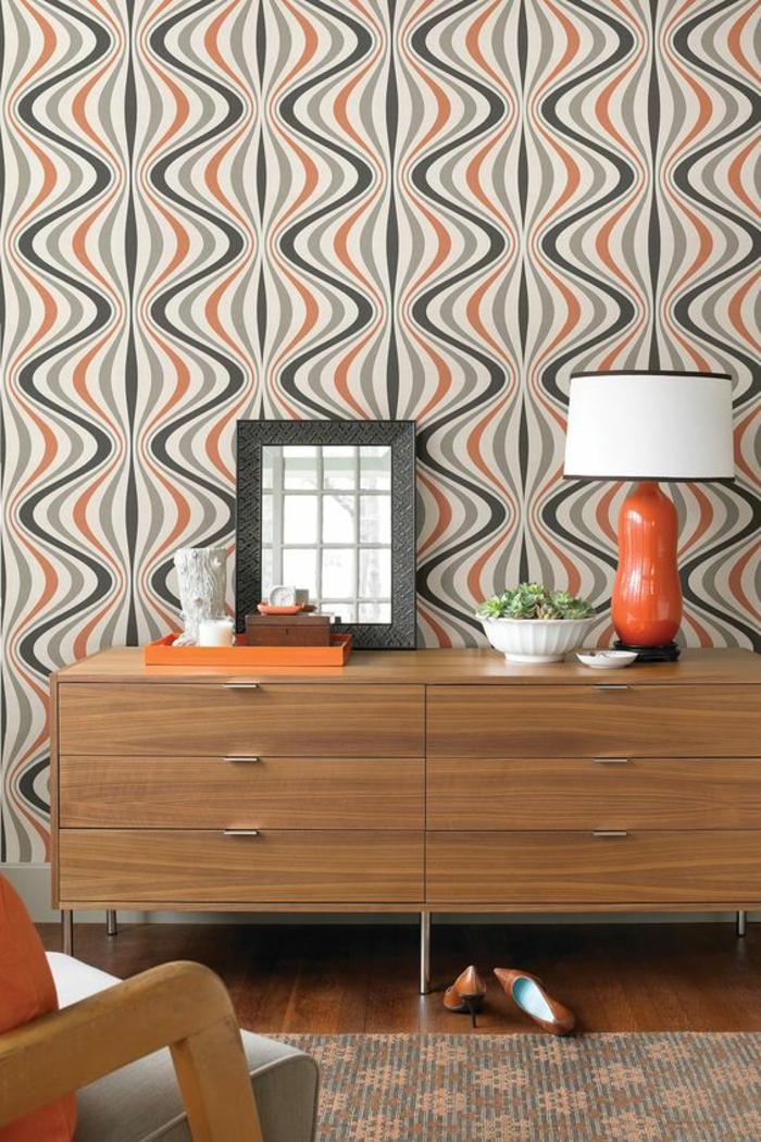 du papier peint pour la déco murale en orange et noir, habiller un mur avec des motifs graphiques ondulants, style rétro années 70