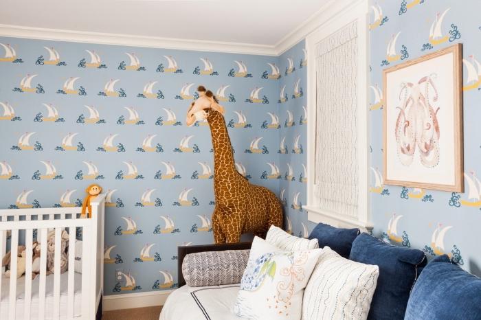 modèle de deco chambre garcon avec papier peint bleu clair à design marine et une peluche grande en forme de girafe